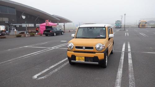 霧に包まれている道に駅と愛車