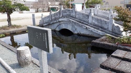孔子公園内にある橋が架かった池と論語説明看板